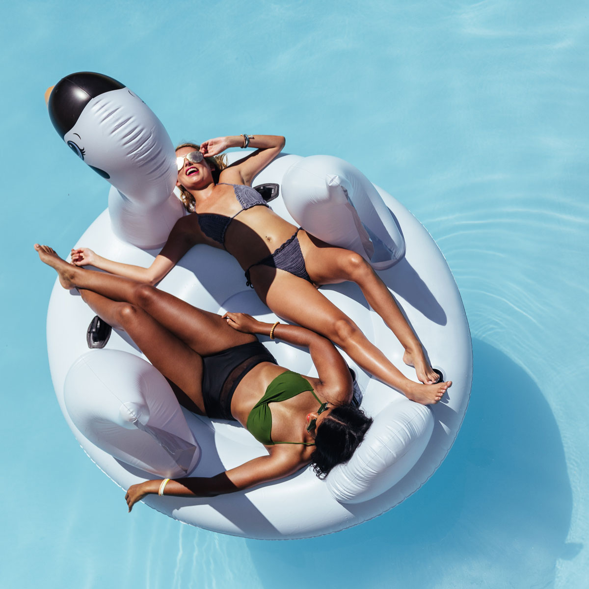 Two Women Laying on Floaty in Pool
